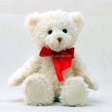 Pure white sitting plush teddy bear with red bow