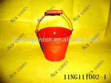 red metal bucket with wooden handle