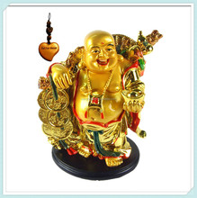 Golden happy laughing buddha statue with a ingot and money for feng shui